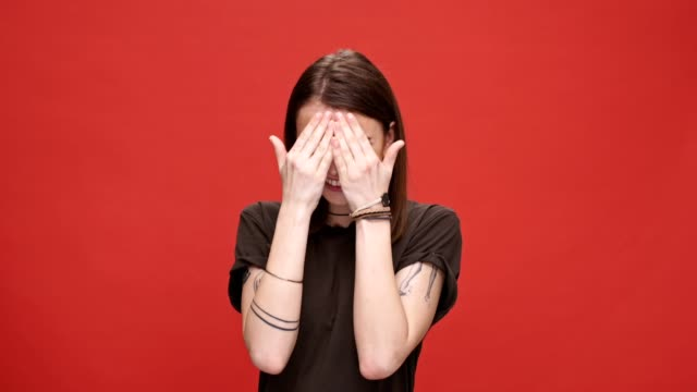 Smiling young girl playing hide and seek while covering her eyes with palms isolated over red background video