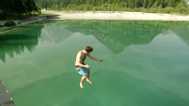 SLOW MOTION: Smiling young man jumping cheerfully into the beautiful mountain lake on a sunny summer day video