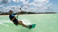 SLOW MOTION: Smiling young surfer woman kiteboarding in beautiful blue lagoon video