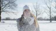 SLOW MOTION: Smiling young woman blowing snow kiss video