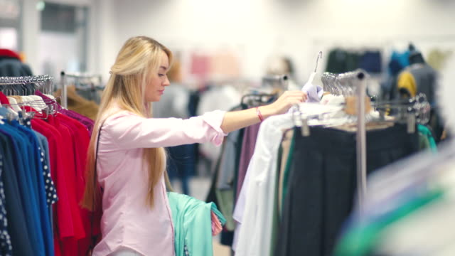 Smiling young woman choosing clothes in a clothing store video
