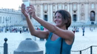 Smiling young woman doing selfie with her smart phone in front of saint peter video