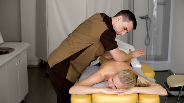 Smiling Young Woman Getting Massage Treatment From Masseuse video