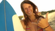 Smiling young woman showing surf sign with her hand video