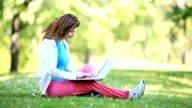 Smilng young woman typing on laptop in the park. video
