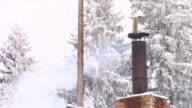Smoke coming out of brick chimney from chalet in mountains, winter season video