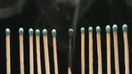 SLOW MOTION: Smoke of single burned matchstick between row of new matchsticks video