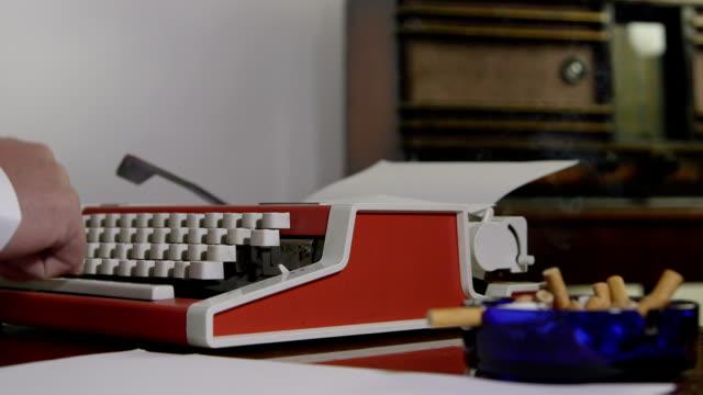 Smoking man typing on a portable typewriter video