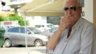 Smoking senior man in the street video