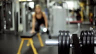 Smooth focus on a woman engaged in gym with dumbbells at bench video