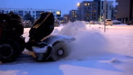 snow blower clean footpath in living house parking in winter at night. video