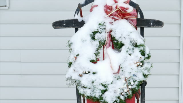 Snow Covered Sleigh with Holiday Wreath Gets Shaken Off. video
