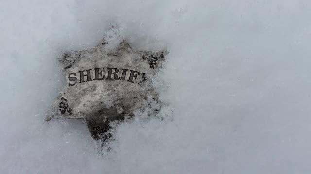 Snow falling on sheriff badge. video