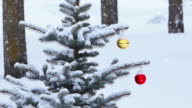 Snow gently falling on Christmas ornaments hanging from tree video