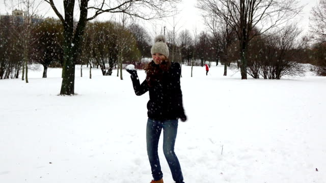 POV snowball fight, woman turn away, then throw snow ball and hit camera video