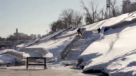 Snowboarder doing boardslide on a ledge in the street video