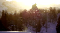 Snowboarder jumping at sunset video