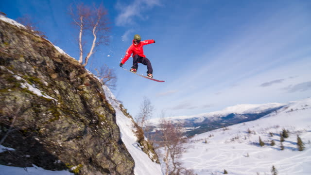 Snowboarder jumping off a cliff, landing on freshly fallen snow video