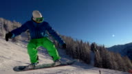 SLOW MOTION: Snowboarder jumping ollie into camera at sunrise in snowy mountains video