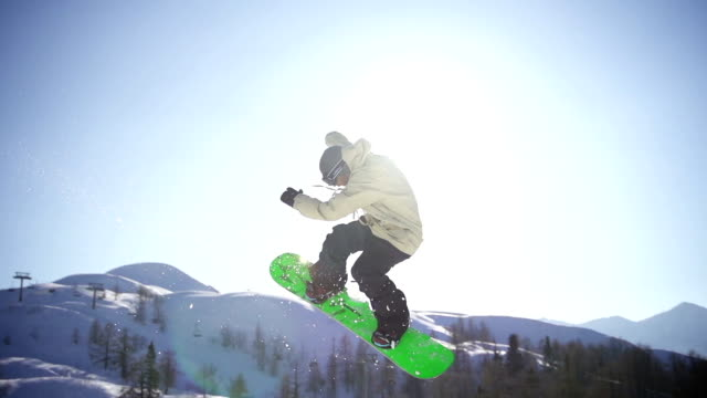 Snowboarder jumps in a snow park video