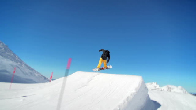 Snowboarder jumps in a snowpark video