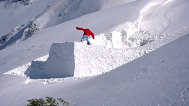 Snowboarder jumps on freshly fallen snow video