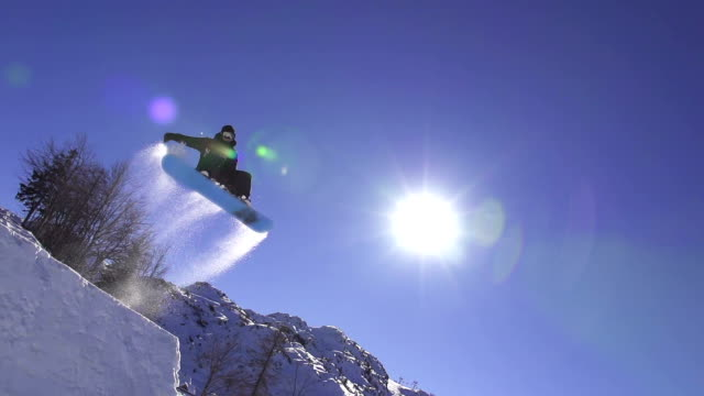 SLOW MOTION: Snowboarder jumps over kicker, low angle view video