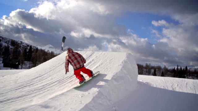 Snowboarder performs a trick in a snowpark video