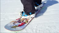SLOW MOTION CLOSE UP: Snowboarder riding and falling on ski slope in sunny ski resort video