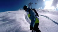 CLOSE UP: Snowboarder riding powder on a sunny winter day video