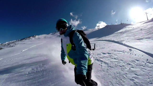 SELFIE: Snowboarder riding powder snow in mountain ski resort video