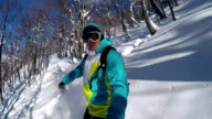 SLOW MOTION CLOSE UP: Snowboarder riding powder snow off piste in the mountains and doing powder turns video