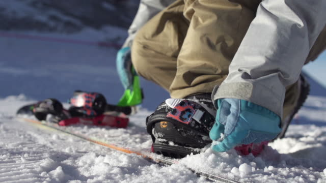 Snowboarder strapping in video