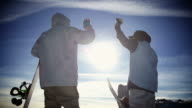 Snowboarders high fiving on top of a mountain video