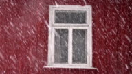 Snowfall and window in old village house video