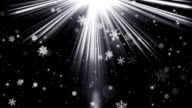 snowflakes in light beams on black loopable background video