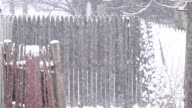 Snowing sideways along the picket fence line slow motion video