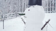 Snowman at the backyard under the snowfall in the winter's day video