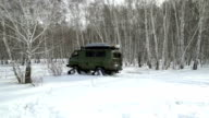 Snowmobile rides through deep snowdrifts in the winter woods video