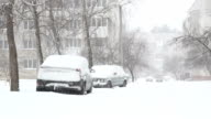 Snowstorm and snow covered street with parked cars. video