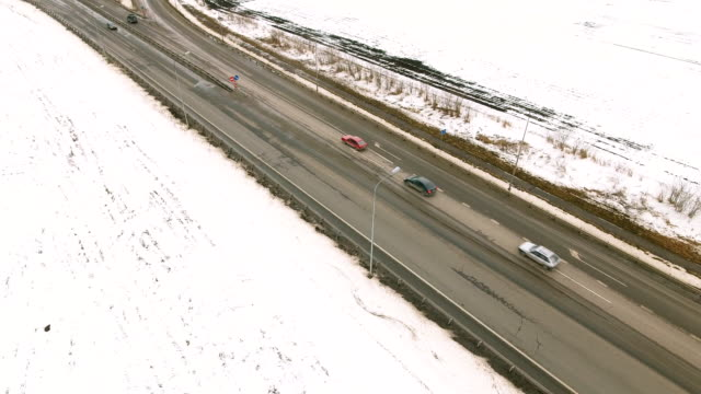 Snowy and frozen winter road with a moving car on it. video