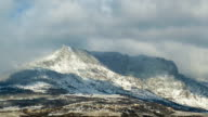 Snowy clouds and sun over mountains, time lapse video