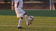A soccer player juggles a ball at sunset video