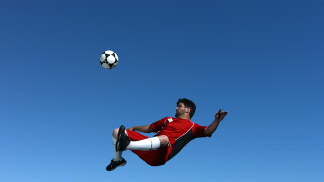 Soccer player kicking ball in mid-air, slow motion video