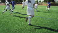 A soccer player shoots a goal during a game and misses video
