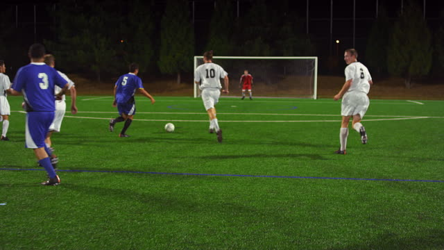 Soccer players pass the ball down the field at night and make a goal and celebrate video