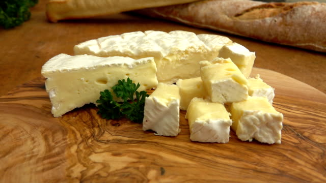 Soft brie cheese cubes on rustic board video