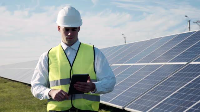 Solar panel technician using tablet near array video