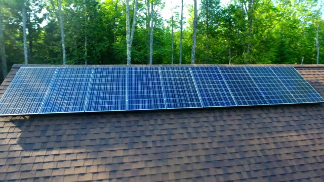 Solar panels on a roof in the forest helping reduce energy costs video