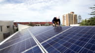 Solar technician installing solar panels on roof. video